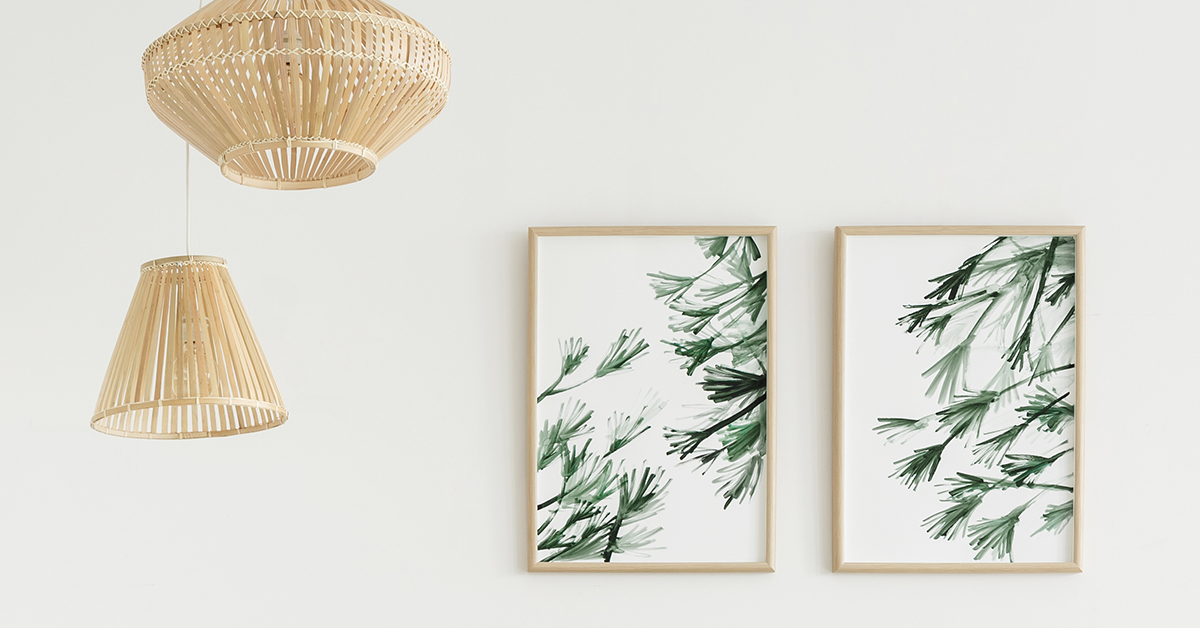 home decor accents wicker lamps and wooden framed leafy art on a clean wall